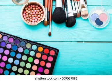Colorful cosmetics on blue wooden workplace. Top view and picturesque