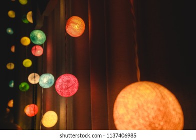 Colorful cotton ball lights used to decorate in Christmas festival and night party decorate on wall with Curtain background for party background.Selective focus.Vintage Night film Tone