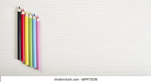 Colorful crayons on white plank background