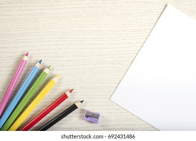 Colorful crayons and white sheet of paper on white plank background