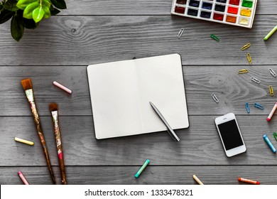 Colorful creative artist table with blank notebook for work sketches and paints, art paintbrushes supplies set on grey wooden background, top view, copy space, flat lay style, drawing class education