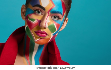 Colorful, creative and artistic pop art make up. Beautiful model looking at camera, posing. Funky and stylish woman has plump lips with pink lipstick. Blue background.