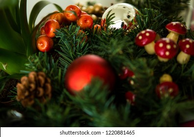 A colorful Cristmas decoration with plastic Cristmas tree branch wiht artificial berries and mushrooms on it.