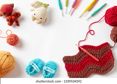 Colorful crochet project with hook and yarn, on white background.