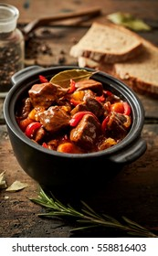 Colorful crock of Hungarian beef goulash seasoned with paprika, bay leaves and sweet peppers on a rustic wooden kitchen table with scattered ingredients