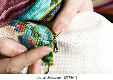 Colorful cross stitch art in the making, showing various color threads and a womans hands working with a needle.