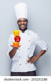 Colorful culinary. Confident young African chef in white uniform holding multi colored peppers and looking at camera with smile while standing against grey background