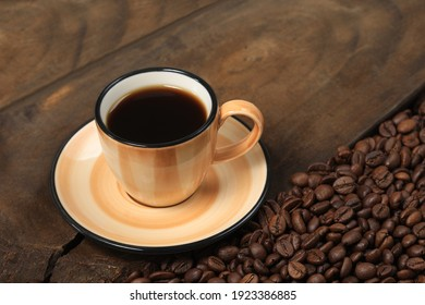 Colorful cup and coffee beans on wood.