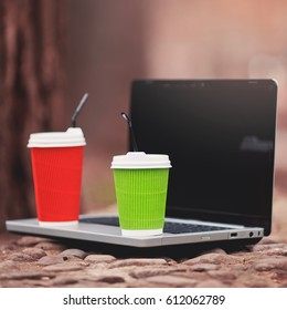 Colorful cup of coffee on laptop.