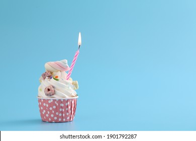 Colorful cupcake with candle isolated in blue background