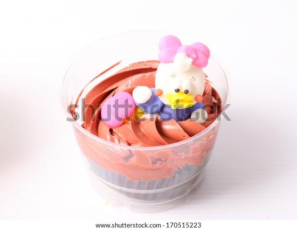 A colorful cupcake with doll on top , isolated