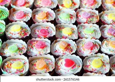 colorful cupcakes as background.