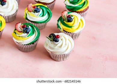 Colorful cupcakes on pink background Above Place for text Beautiful cupcakes decorated with berries