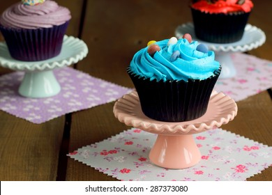 Colorful cupcakes on a wooden rustic table
