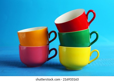 Colorful cups on blue wooden background