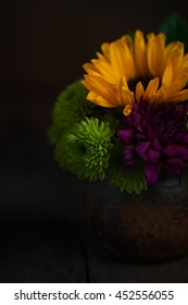 Colorful Cut Flowers in Clay Pot on Vintage Wood Table