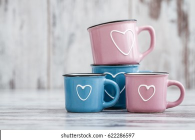 Colorful cute coffee mugs on white wooden background