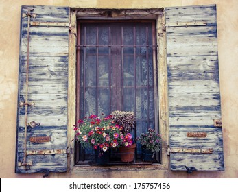 Colorful daisy flowers and cactus in pots placed on the window of the old stone house. Closed window with lace curtain, rusty lattice and open wooden shutters. (Arles, Provence, France) Toned image.