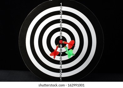 Colorful darts hitting a target, isolated on black