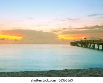 colorful dawn along atlantic ocean at lake worth pier in south florida