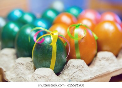 colorful decorated Easter eggs in egg carton holder, holiday background
