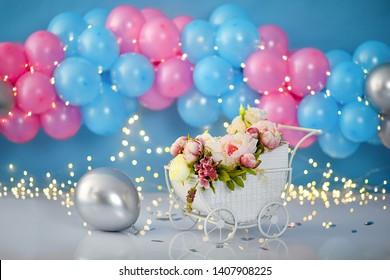 Arrière-plan décoratif coloré avec poussette, fleurs et ballons pour une première fête d'anniversaire
