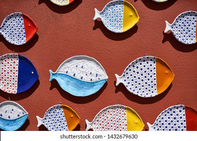 Colorful decorative ceramic plates in a form of fishes are hanging on the textured terracotta wall outdoors. They are white with red, blue, yellow, cyan and orange. Sun shines onto them. Closeup.