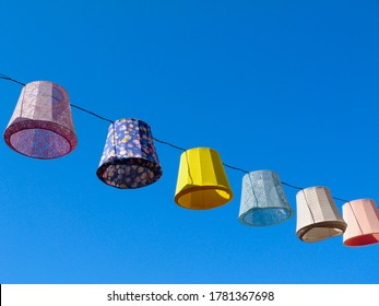 colorful decorative exterior canvas lamp shades, lanterns or lampions above public street above town street in Europe. festival and summer vacation mood.
