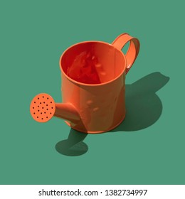 Colorful decorative watering can for gardening on green background