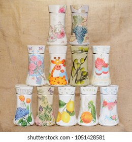 Colorful decoupaged jars arranged in a triangular manner, on a jute background. Decoupage has different decorative motifs. One of the jars has written on it word Flowers in French.