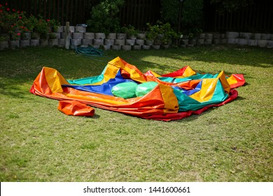 A colorful deflated jumping castle on a green lawn. This image can be used to represent the concept of a party being over or the setting up for an event.