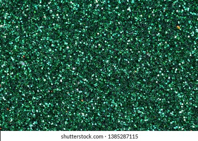Colorful defocused emerald green background with glittering and sparkling spots