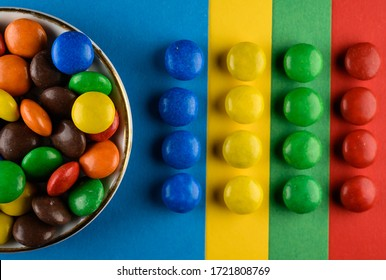 Colorful delicious chocolate candies or buttons  lying in several rows, forming a square. Sweets sorted by color. Isolated on a colorful background. Food background.