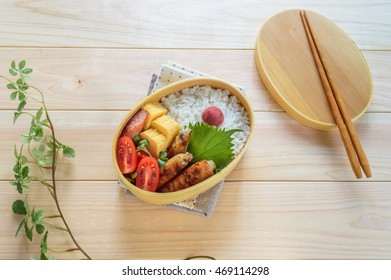 colorful and delicious looking bento (a lunch box) on wooden table