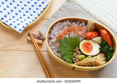 A colorful and delicious looking bento consisting of stir fry bamboo shoot with ground pork, brown rice, boiled egg, sausage and salmon fuirkake seasoning