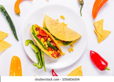 Colorful delicious mexican tacos, on the white plate, decorated with vegetables and nachos