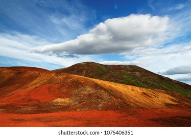 Colorful deposits of volcanic ash in reds and yellows against a green hill, above blue sky with a striking cloud formation - Location: Iceland, Golden Circle