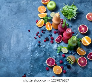 Colorful detox smoothie in bottles, with spinach, berries, mango, kiwi, lime. Summer diet fresh vegan drink for breakfast or snack, copy space background