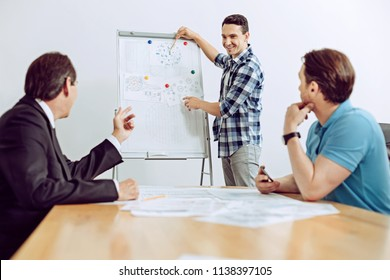 Colorful diagrams. Cheerful emotional happy engineer showing bright diagrams while his coworkers looking at him