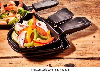 Colorful diced fresh sweet peppers and mushrooms for adding to raclette cheese ready in a small metal skillet on a rustic wooden table for traditional Swiss cuisine