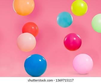 Colorful different balloons with pink background
