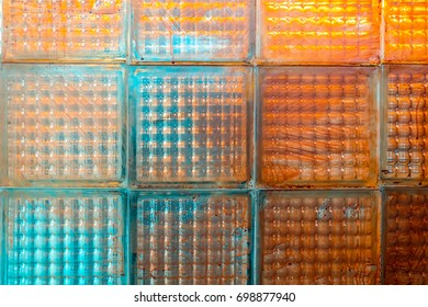 Colorful and dirty toilet glass tile wall in neon blue and orange color, close up background texture.