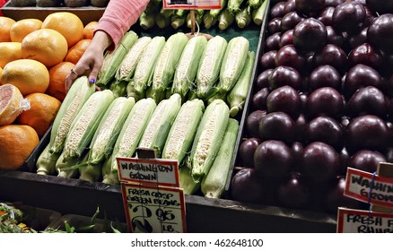 Colorful display of fruits and vegetables with a hand stacking fresh corn on the cob at an outdoor market in Seattle.