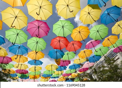 Colorful display of hanging umbrellas, covering the sky, to create a festive mood.