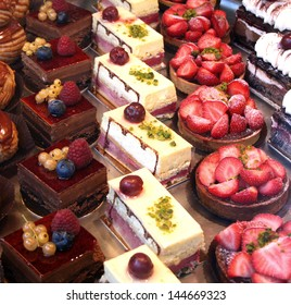 Colorful display of pastries topped with fruits (shallow depth of field)