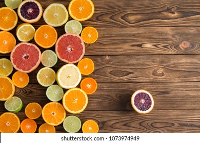 Colorful display of a variety of cut citrus fruits with oranges, grapefruit, clementine, lime, lemon and blood oranges with a single blood orange set to the side on a wooden background