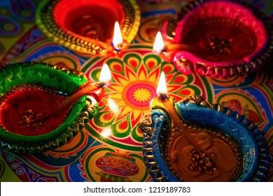 Colorful Diwali clay diya lamps on rangoli for festival background