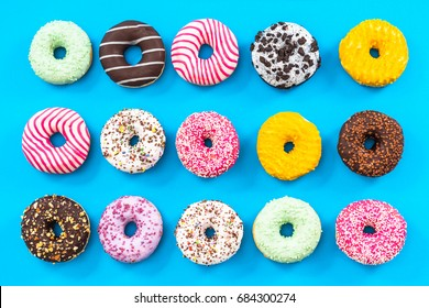 Colorful donuts border background, flat lay top view