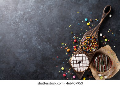 Colorful donuts and candies on stone table. Top view with copy space