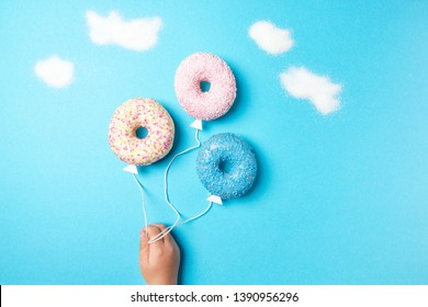 Colorful donuts on blue background, creative food minimalism, donuts in a shape of balloon in the sky with clouds made of sugar, top view